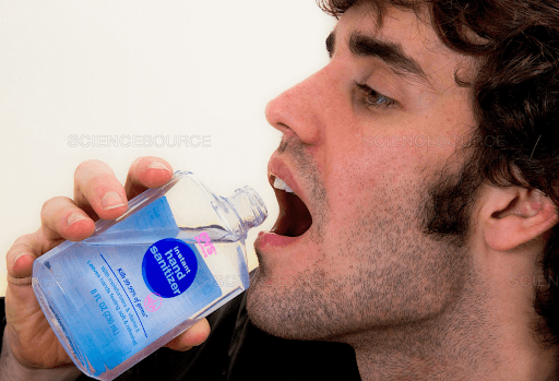 man drinking hand sanitizer